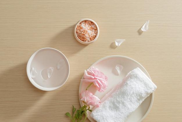 Impostazione spa di sale, asciugamano, fiore sulla piastra su uno sfondo di legno con spazio di copia. rilassare. avvicinamento. vista dall'alto.
