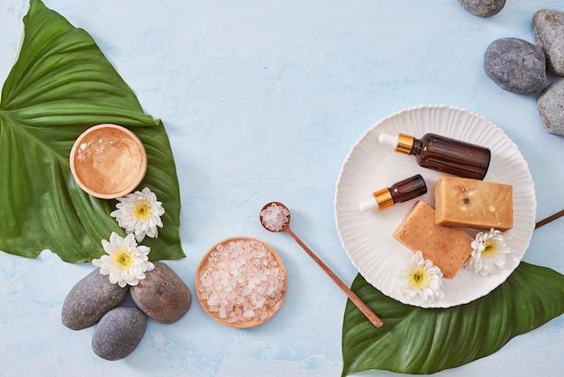 Ambiente termale con crema cosmetica, gel, sale da bagno e foglie di felce su sfondo blu