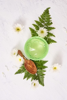 Impostazione spa con gel cosmetico, foglie su sfondo bianco tavolo