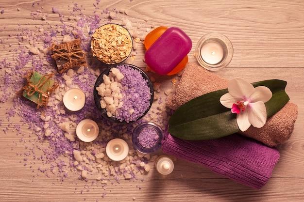 Ambiente termale con fiori di orchidea, ciotola con sale marino, sapone aromatico, scrub, candele e asciugamani su tavola di legno