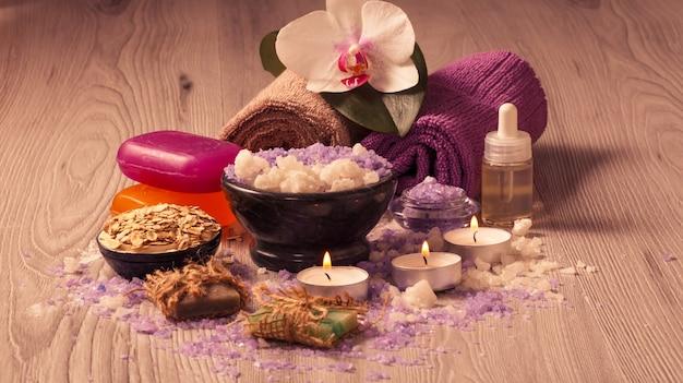 Ambiente termale con fiori di orchidea, ciotola con sale marino, bottiglia con olio aromatico, sapone, scrub, candele e asciugamani su tavola di legno