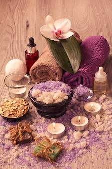 Ambiente termale con fiori di orchidea, ciotola con sale marino, bottiglie con olio aromatico, sapone, scrub, candele e asciugamani su tavola di legno