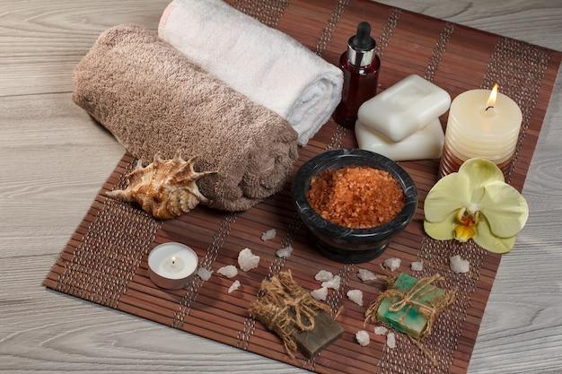 Impostazione spa con fiori di orchidea, ciotola con sale marino, conchiglia, bottiglia con olio aromatico, sapone, candele e asciugamani su tovagliolo di bambù