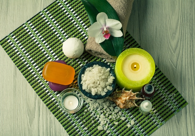 Impostazione spa con fiori di orchidea, ciotola con sale marino, conchiglia, bottiglie con olio aromatico, sapone, candele e asciugamano su tovagliolo di bambù