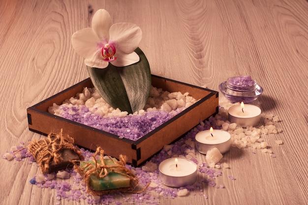 Ambiente termale con fiori di orchidea, scatola con sale marino, sapone aromatico e candele su tavola di legno