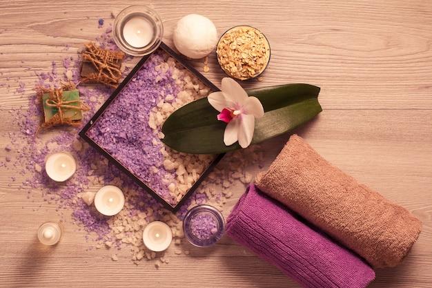 Ambiente termale con fiori di orchidea, scatola con sale marino, sapone aromatico, scrub, candele e asciugamani su tavola di legno