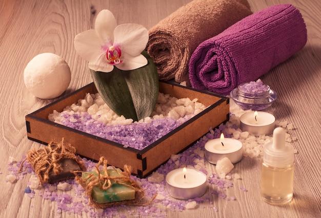Ambiente termale con fiori di orchidea, scatola con sale marino, bottiglia con olio aromatico, sapone, candele e asciugamani su tavola di legno