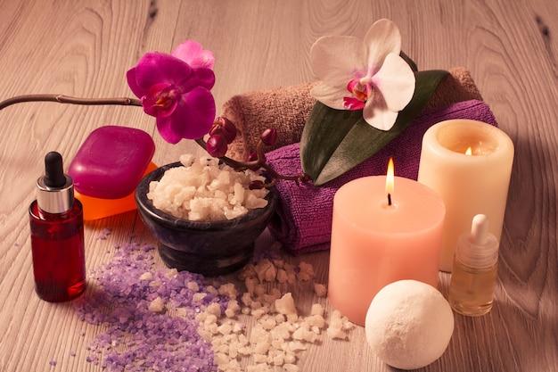 Ambiente termale con fiori di orchidea, ciotola con sale marino, bottiglie con olio aromatico, sapone, candele e asciugamani su tavola di legno
