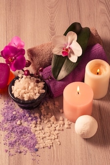 Ambiente termale con fiori di orchidea, ciotola con sale marino, candele, sapone e asciugamani su tavola di legno