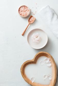 Impostazione spa con ciotola di latte di riso, fiori, sale, sapone, olio e asciugamano su sfondo bianco