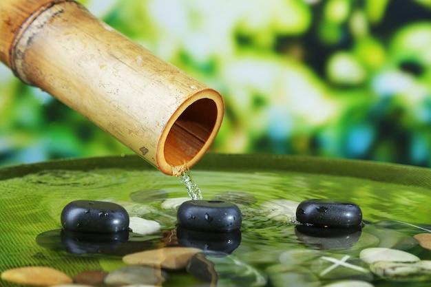 Spa ancora in vita con fontana di bambù, su sfondo luminoso