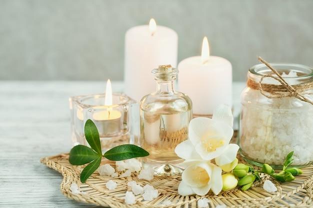 Spa ancora in vita con profumo e bottiglia di olio aromatico circondato da fiori di fresia, sulla superficie chiara