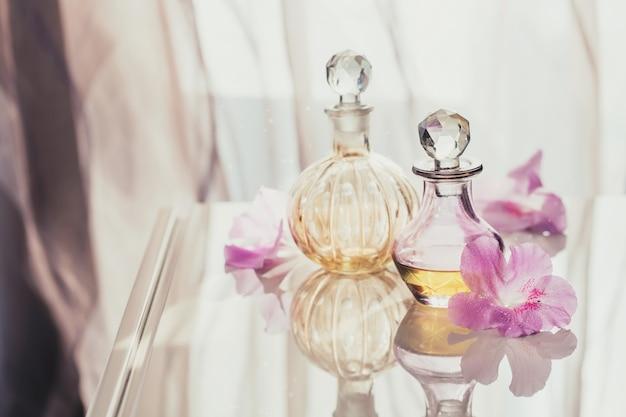 Spa ancora in vita con bottiglie di profumo e oli aromatici circondate da fiori, sulla superficie chiara