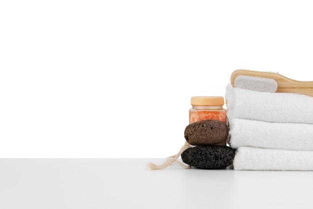 Spa ancora in vita con impilati di pietra e asciugamano isolato su bianco