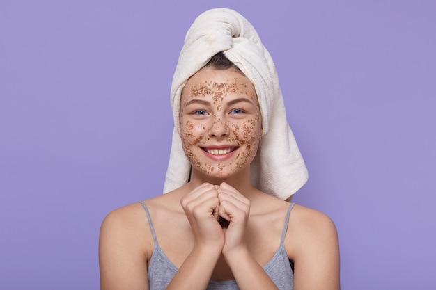Ragazza teenager della stazione termale che applica la maschera facciale dell'argilla, asciugamano bianco d'uso sopraelevato