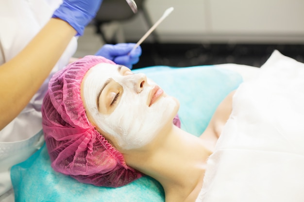 Terapia della stazione termale per la giovane donna che ha maschera facciale al salone di bellezza.