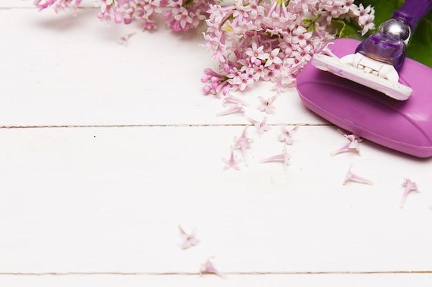 Asciugamani spa e sapone e fiori lilla su un tavolo di legno bianco