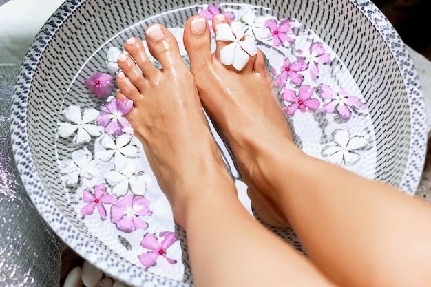 Trattamento termale e prodotto per i piedi della donna. pediluvio nella ciotola con fiori tropicali, thailandia. concetto sano.