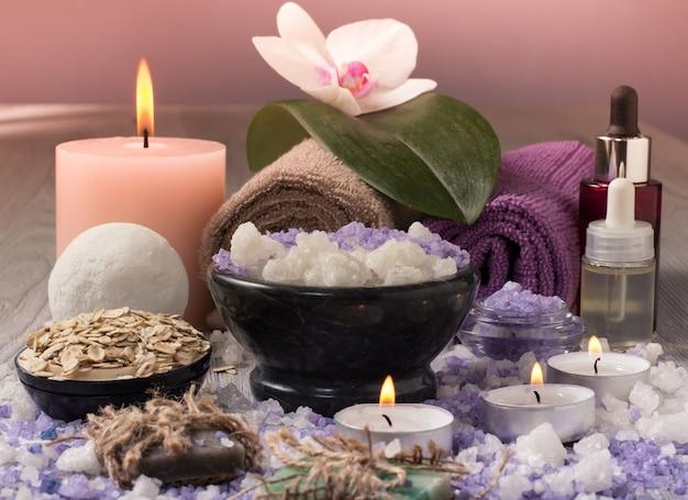 Prodotti per il trattamento termale con fiori di orchidea, ciotola con sale marino, bottiglie con olio aromatico, sapone, scrub, candele e asciugamani su tavola di legno
