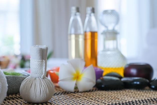 Set di trattamenti termali e olio da massaggio aromatico sul massaggio del letto. ambiente thailandese per aromaterapia e massaggio con fiori sul letto, relax e cure salutari.