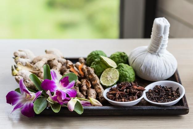 Set di trattamenti termali con dabber, scrub, bergamotto, fiori di orchidea, erbe e pennello in vassoio di legno vicino alla finestra. accessorio per trattamenti di bellezza biologici e naturali in salone