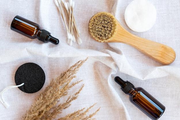 Spa e concetto di benessere con sale marino, pampa secca, pennello, olio e spugne per il viso su sfondo tessile, vista dall'alto