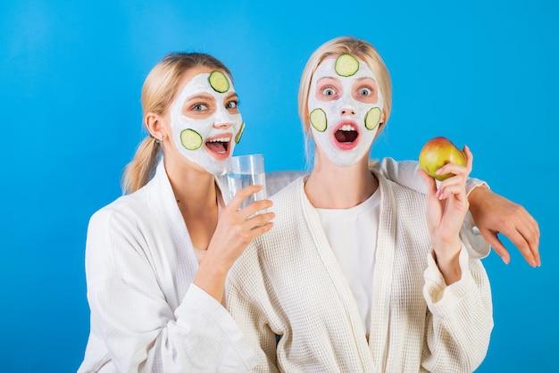 Terme e benessere. sorelle degli amici delle ragazze che fanno la maschera facciale dell'argilla maschera antietà. rimani bella. cura della pelle per tutte le età. donne che si divertono con la maschera di pelle di cetriolo. bevi acqua mangia frutta. concetto di salute.