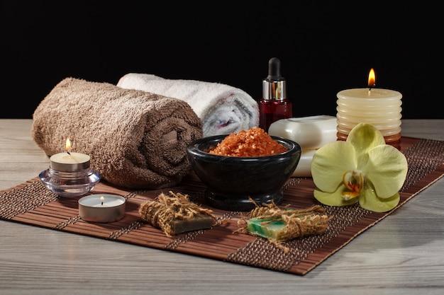 Spa e ambiente benessere con fiori di orchidea, ciotola con sale marino, bottiglia con olio aromatico, sapone, candele e asciugamani su tovagliolo di bambù