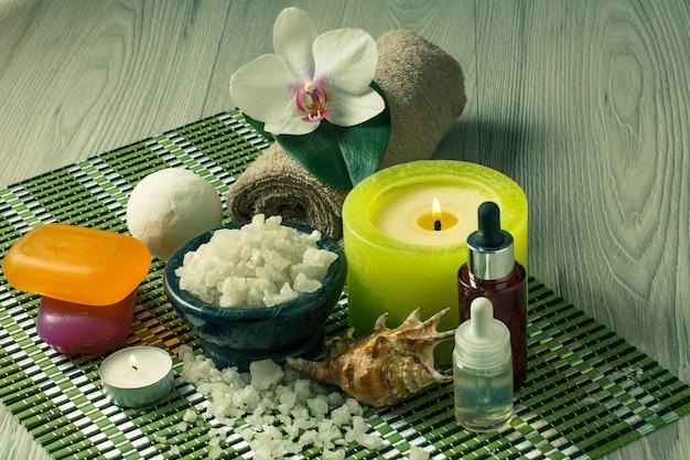 Spa e ambiente benessere con fiori di orchidea, ciotola con sale marino, conchiglia, bottiglie con olio aromatico, sapone, candele e asciugamano su tovagliolo di bambù