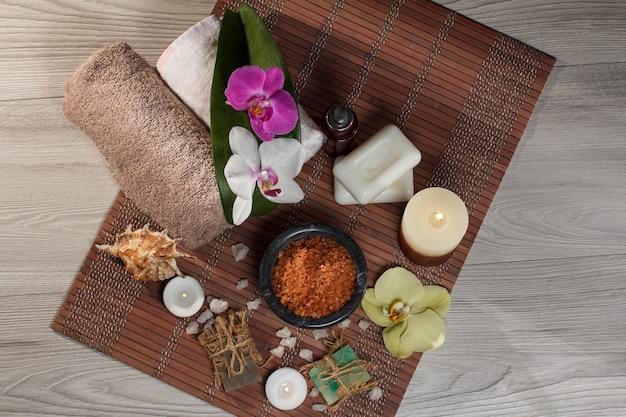 Spa e ambiente benessere con fiori di orchidea, ciotola con sale marino, conchiglia, bottiglia con olio aromatico, sapone, candele e asciugamani su tovagliolo di bambù