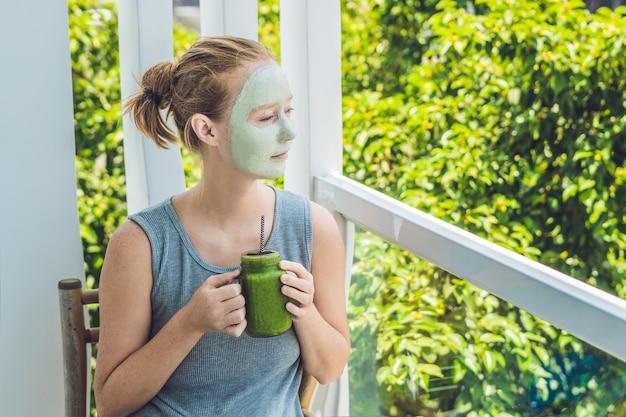 Donna della stazione termale che applica maschera facciale all'argilla verde. trattamenti di bellezza. frullato verde fresco con banana e spinaci con cuore di semi di sesamo. amore per un concetto di cibo crudo sano. concetto di disintossicazione