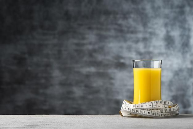 Spazio succo di latte di mais in vetro con sfondo di cibo di misura di nastro