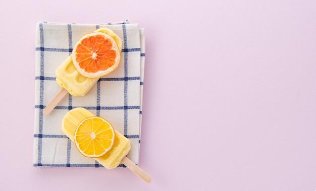 Spazio gelato bastoncino di limone su sfondo rosa pastello