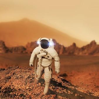 L'astronauta dell'uomo dello spazio cammina sul pianeta rosso marte. l'uomo viaggia su marte. astronauta in atterraggio nel deserto rosso