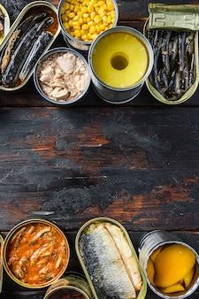 Spazio per il testo tra due righe di varie verdure preparate in scatola, carne, pesce e frutta in barattoli di latta. su uno sfondo di legno vista dall'alto verticale.