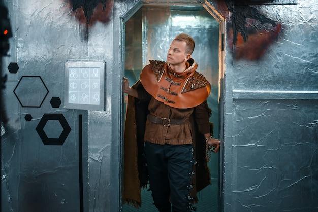 Il viaggiatore spaziale guarda fuori dal teletrasporto con pareti di alluminio. astronave fantasy per viaggi interstellari, scienza e tecnologia future, navetta futuristica