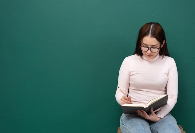 Donne dello spazio con il libro sulla parete verde
