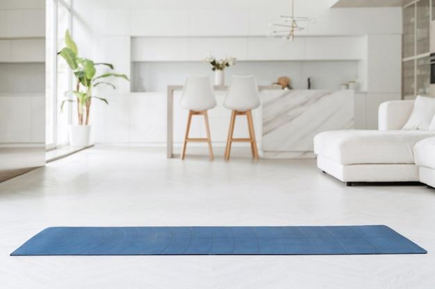 Spazio per lezione di yoga a casa. tappetino per esercizi di yoga, fitness o allenamento a casa, in soggiorno