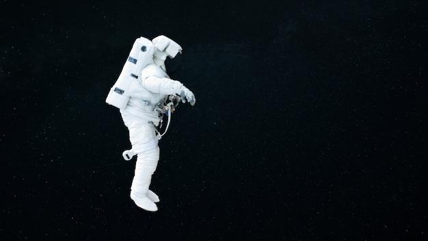 Spaceman vola nello spazio aperto su uno sfondo stellato scuro. l'astronauta inizia una missione. cosmo e umano