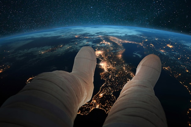 Spaceman si siede e guarda il pianeta terra blu con le luci notturne delle città dallo spazio. piedi di astronauta sullo sfondo della terra. carta da parati del cosmo. uomo che riposa in orbita