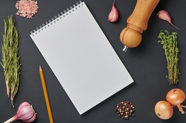 Spazi, condimento e taccuino bianco con matita. modello di carta per notebook per ricevuta di cibo, menu o concetto di blog alimentare. vista dall'alto
