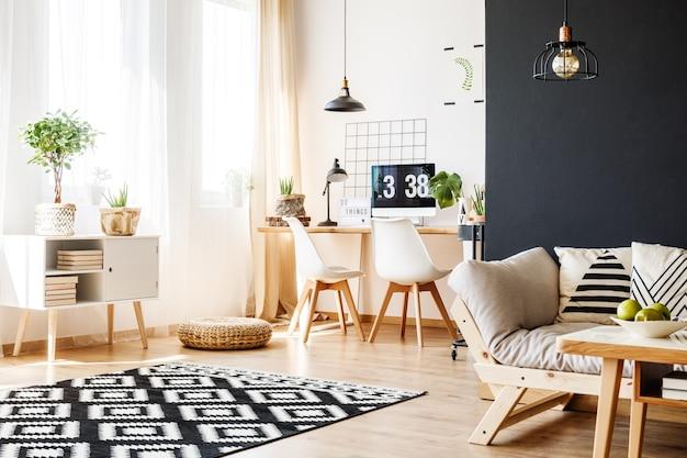 Spaziosa camera luminosa con moquette a motivi geometrici, parete nera, divano e spazio di lavoro con mobili scandinavi