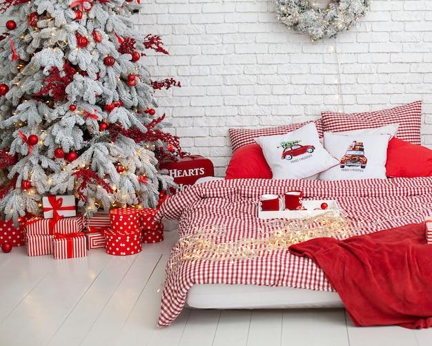 Spaziosa camera da letto luminosa in stile loft con albero di natale decorato