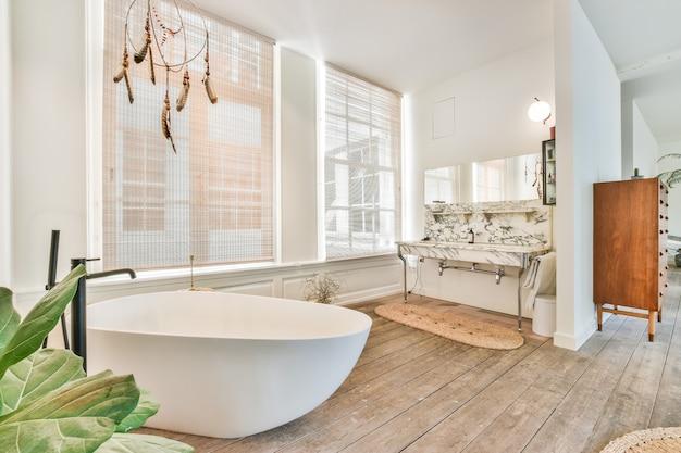 Spaziosa zona bagno aperta con vasca da bagno e doppio lavabo in marmo sotto lo specchio vicino a grandi finestre nelle persiane