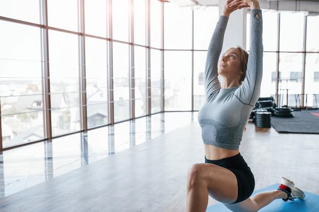 Camera spaziosa. stretching prima degli esercizi. la giovane donna allegra ha una giornata di fitness in palestra al mattino