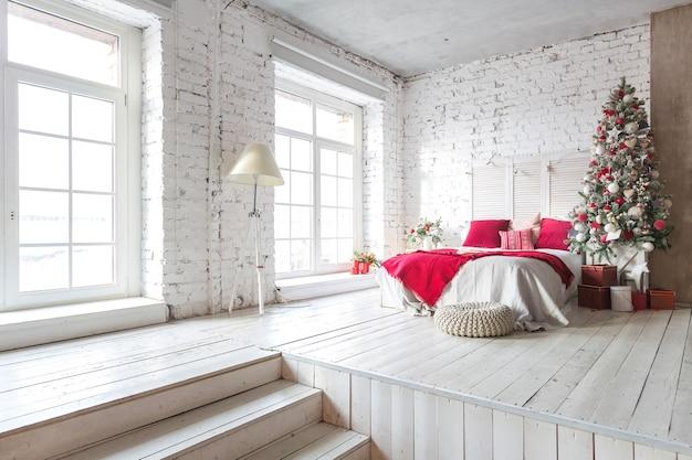 Una spaziosa camera da letto con luce bianca in stile loft con un albero di natale decorato e una ghirlanda.