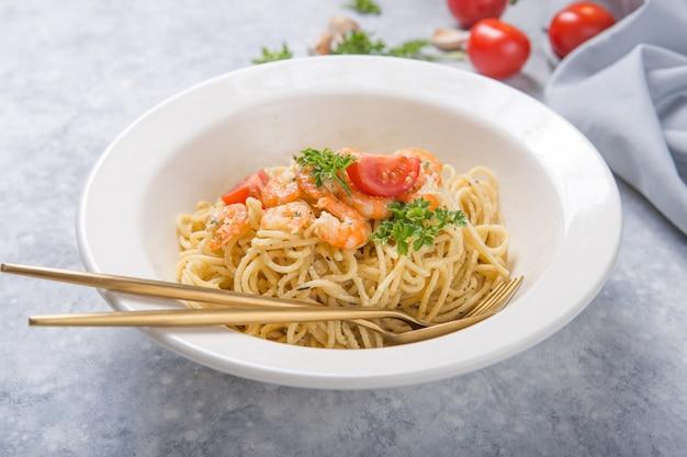 Spagetti alla marinara con shripms. piatto di pasta sul tavolo di cemento grigio