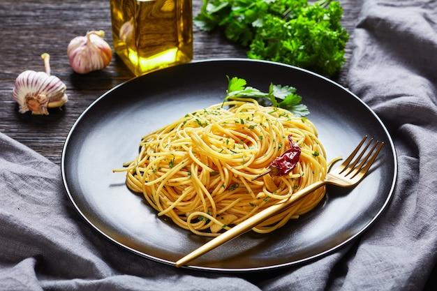 Spaghetti alla colatura di alici, spaghetti conditi con salsa di acciughe, peperoncino, aglio e prezzemolo su una piastra nera con forchetta dorata su un tavolo di legno scuro, vista del paesaggio