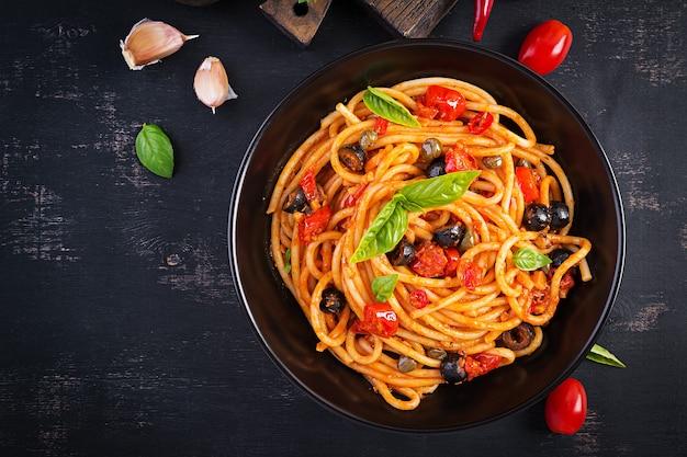 Spaghetti alla puttanesca - piatto di pasta italiana con pomodori, olive nere, capperi, acciughe e basilico. vista dall'alto, posizione piatta