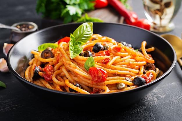 Spaghetti alla puttanesca - piatto di pasta italiana con pomodori, olive nere, capperi, acciughe e basilico.